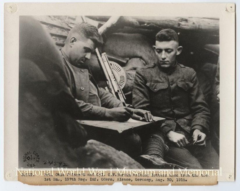 Two U.S. soldiers write letters home from a foxhole during World War l.