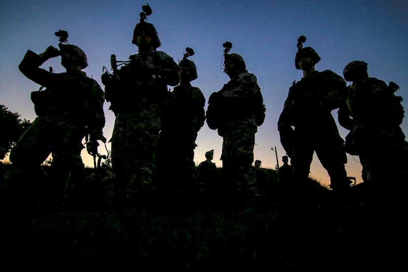 Silhouettes of soldiers are reflected against the sky.