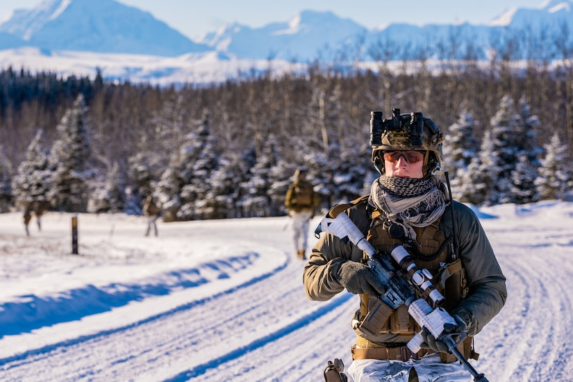 A marine carrying a gun walks in the snow.