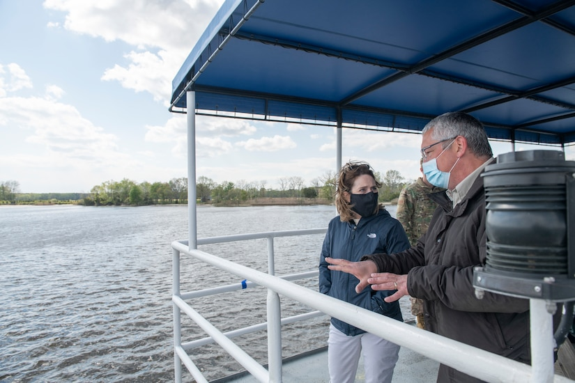 A man and woman speak to each other while standing near a safety rail and under an awning on a boat.