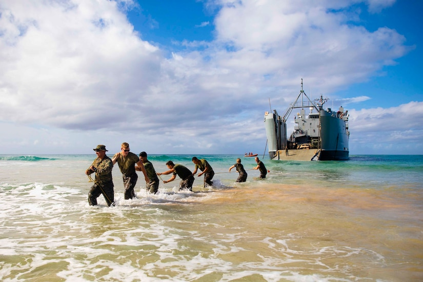 Marines stand on a beach in water up to their knees while pulling a rope connected to a large vessel.