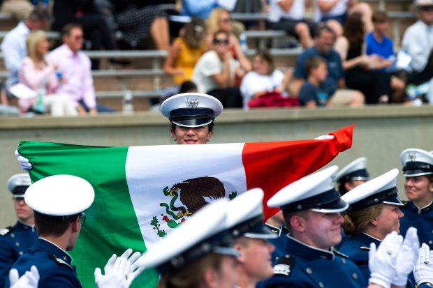 Mexican Navy Cadet Itzel Sinai Chan Topete proudly displays the Mexican flag during a graduation ceremony at the U.S. Air Force Academy, Colorado Springs, Colo., May 26, 2021.