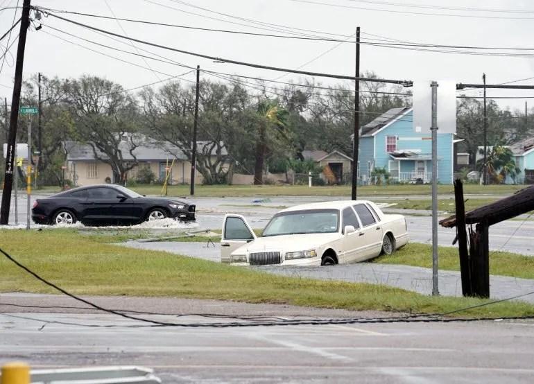 Un automovilista pasa un coche atrapado en las inundaciones después del huracán Harvey en Rockport, Texas, EEUU.