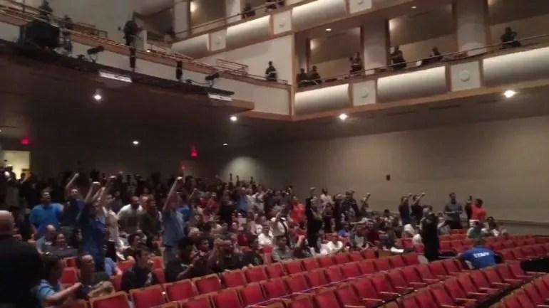Decenas de estudiantes protestan con el puño en alto durante la conferencia del supremacista blanco Richard Spencer en la Universidad de Florida.