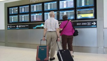 Dos pasajeros verifican hora de salida de su vuelo en el Aeropuerto Internacional de Miami.