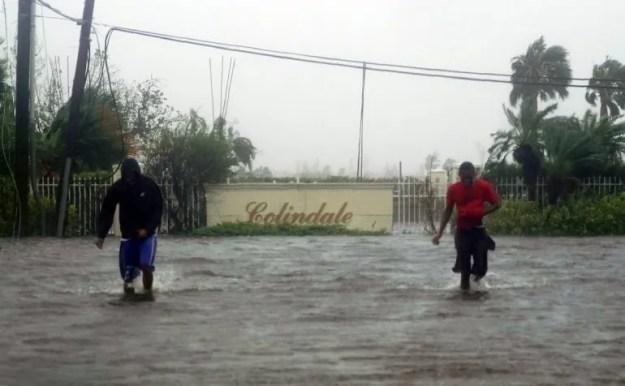 Dos hombres deambulan por una calle inundada de agua afcetada por el huracán Dorian en Freeport, Bahamas, el martes 3 de septiembre de 2019.