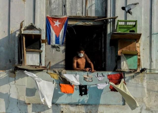Un hombre usa una máscarilla en el balcón de su hogar en La Habana, Cuba el 11 de abril de 2020.