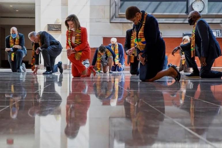 La presidenta de la Cámara de Representantes, la demócrata Nancy Pelosi, al centro, y otros miembros del Congreso se arrodillan y guardan un minuto de silencio el lunes 8 de junio de 2020 en el Capitolio en Washington, en honor de George Floyd.