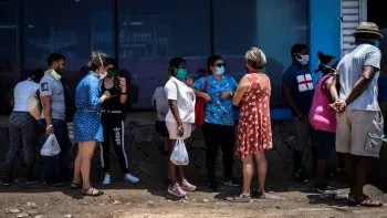 Afuera de una tienda estatal de comida, personas con mascarillas para protegerse del nuevo coronavirus esperan en línea para entrar en La Habana, Cuba, el martes 19 de mayo de 2020.