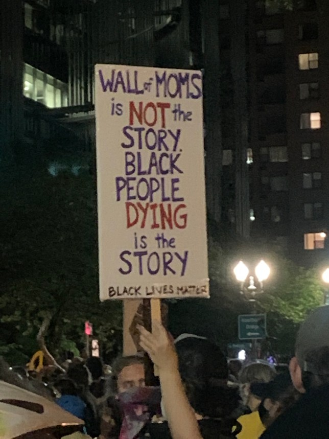 Sign reads: Wall of Moms is not the story. Black people dying is the story. Black lives matter.