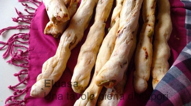Bastoncini di pane con olive e pomodori secchi