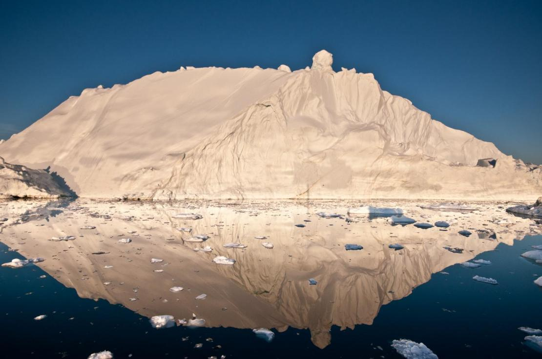 The midnight sun casts a golden glow on an iceberg and its reflection in Disko Bay, Greenland. Much of Greenland's annual mass loss occurs through calving of icebergs such as this. Credit Ian Joughin, University of Washington