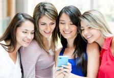 girls-gathered-around-cell-phone