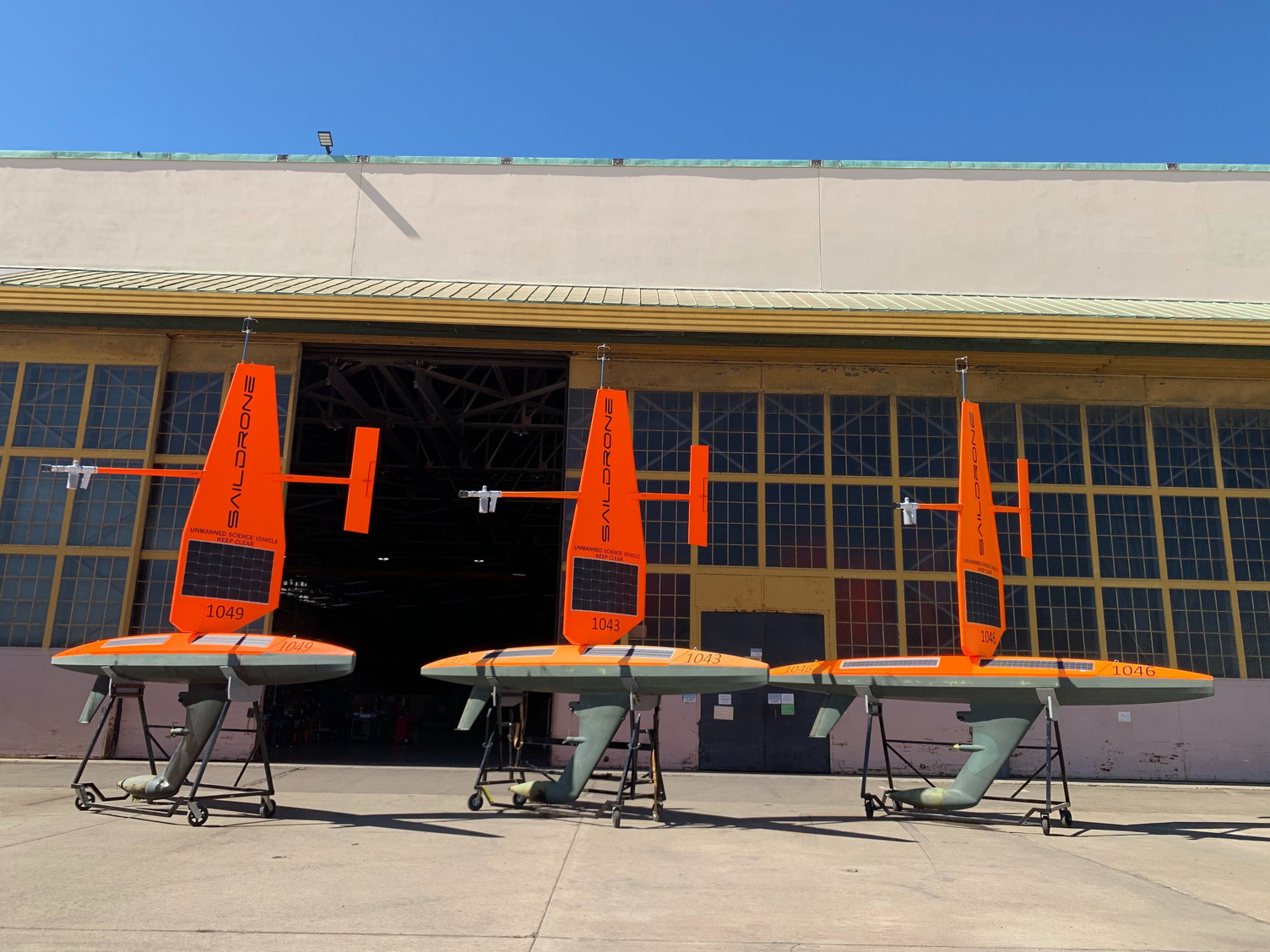 Photo of Saildrones on cradles next to a warehouse hanger.
