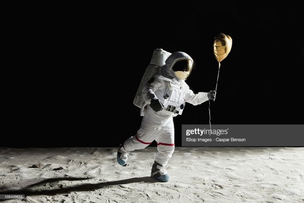 An Astronaut On The Moon Holding A Heart Shaped Helium