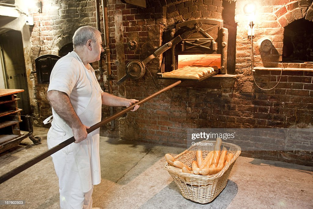 Baker Taking Bread Out Of Oven In Antique Bakery High-Res ...