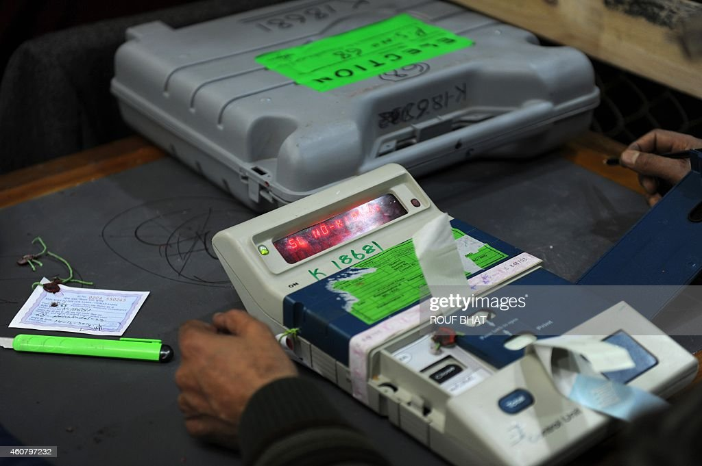 Indian polling officials count votes from an electronic ...