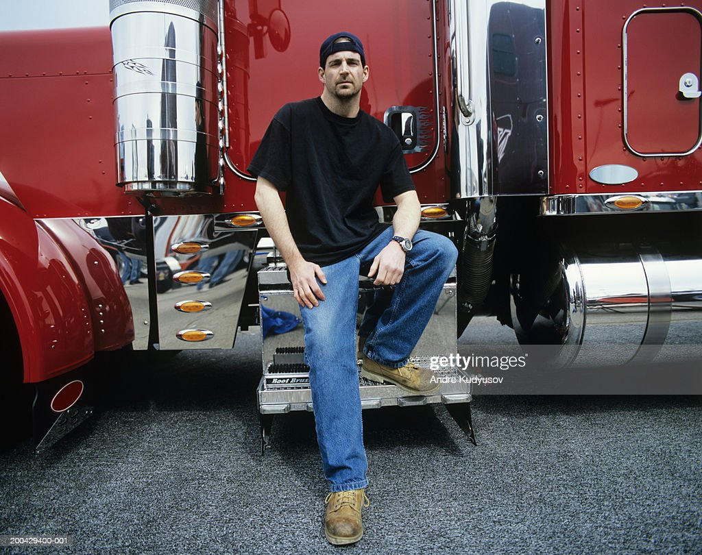 Male Truck Driver Sitting On Steps To Cab Of Truck ...