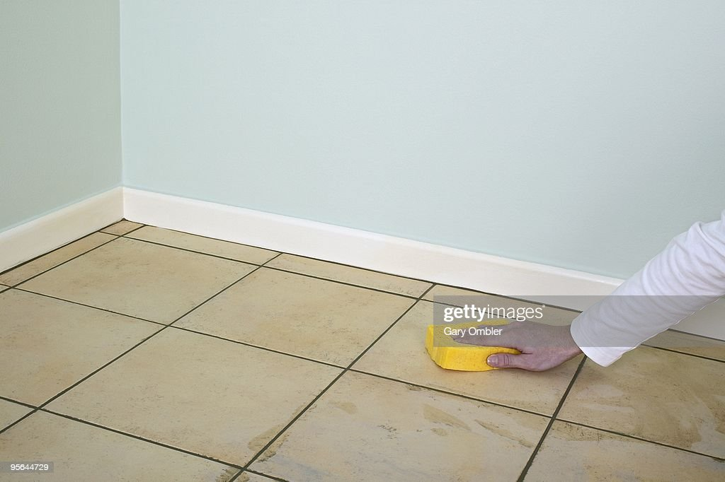 man using sponge to clean grout off tiled floor in room high res stock photo getty images