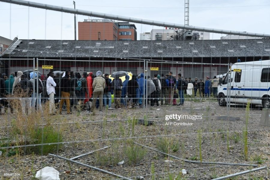 Migrants gather with their belongings to board buses during the     Migrants gather with their belongings to board buses during the evacuation  by the French police of a makeshift camp at Porte de la Chapelle  in the  north of