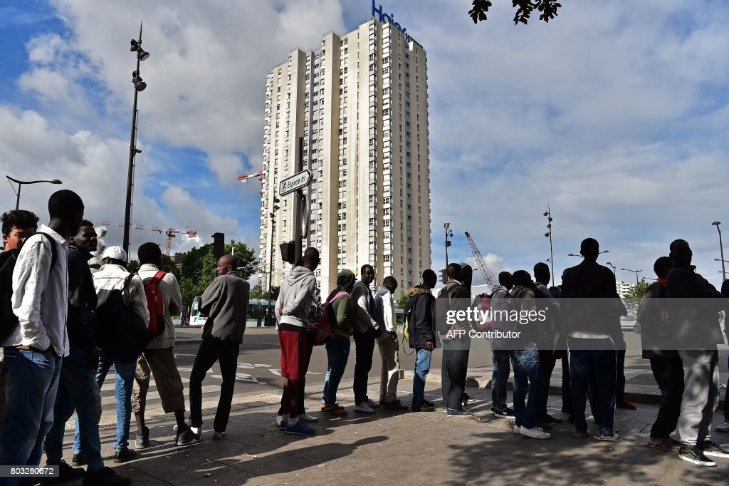 Migrants stand in a queue as they wait to receive food from     Migrants stand in a queue as they wait to receive food from volunteers at Porte  de la Chapelle in Paris on June 29  2017  Some 1 200 people live on the