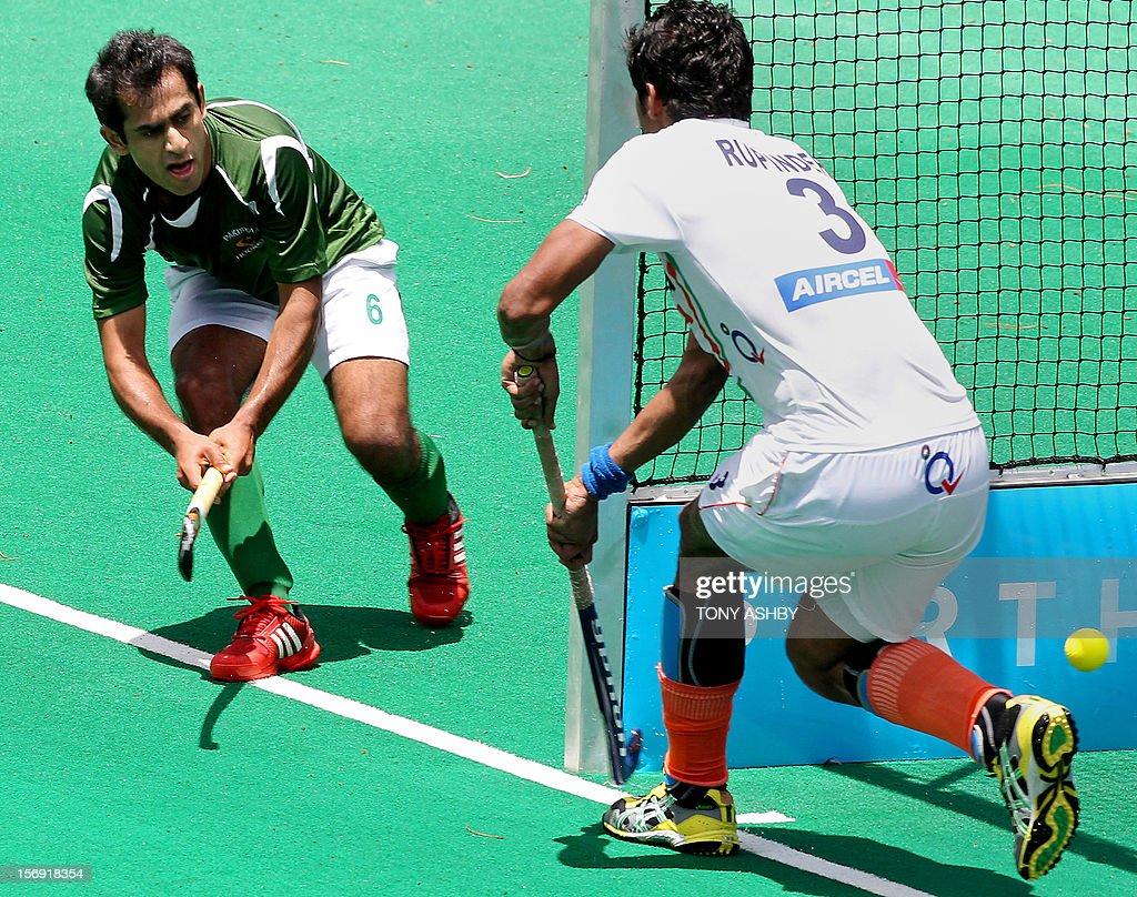 Rashid Mehmood of Pakistan (L) steers the ball past ...