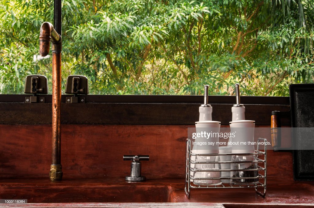 https www gettyimages com detail photo rustic kitchen sink with copper faucet and some royalty free image 1003118364