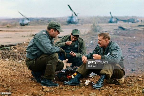 Two American and one Vietnamese soldier relax around a ...