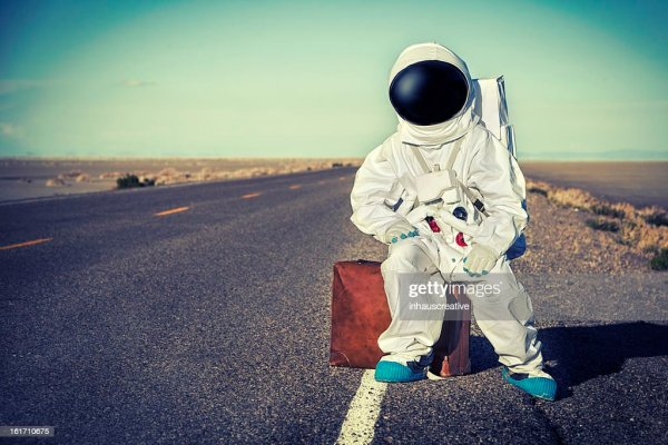 Vintage Astronaut Sitting On Luggage Waiting For A Ride