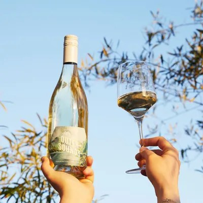 hands holding wine bottle and glass with white wine