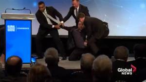 Protester storms stage ahead of Premier Jason Kenney's speech at 2019 Global Petroleum Show