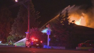 Three men, who were asleep when a fire broke out at their Kelowna home, managed to get out safely thanks to a passer-by