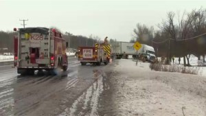 Fire fighters work to clear highway after tractor trailer goes sideways into ditch in Hamilton