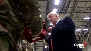 Trump signs red 'MAGA' caps during Germany stopover with U.S. service members