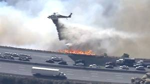 Helicopters drop water on wildfire beside motorists stuck in traffic on California freeway