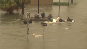 Boat flips as people try to travel through flooded waters in Houston