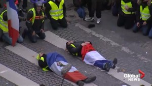 Protesters draped in French flags and yellow vests lie down on the Champs Elysee