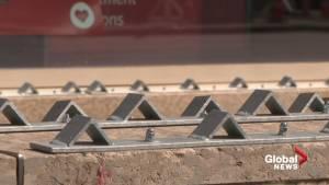 Metal barriers block sitting space on Jasper Avenue