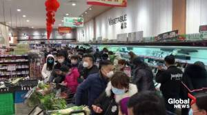 Mask-wearing shoppers queue for groceries in Wuhan as coronavirus death toll rises