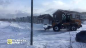 Streets buried by snow as plow begins to clear it