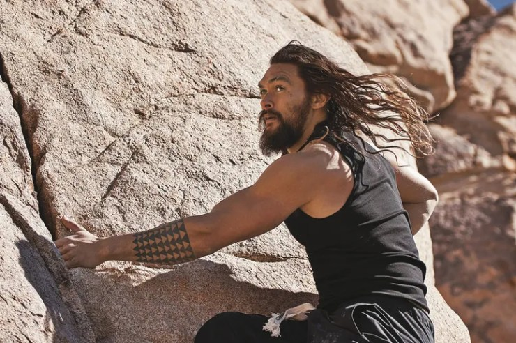 jason momoa rock climbing with hair flowing in the wind