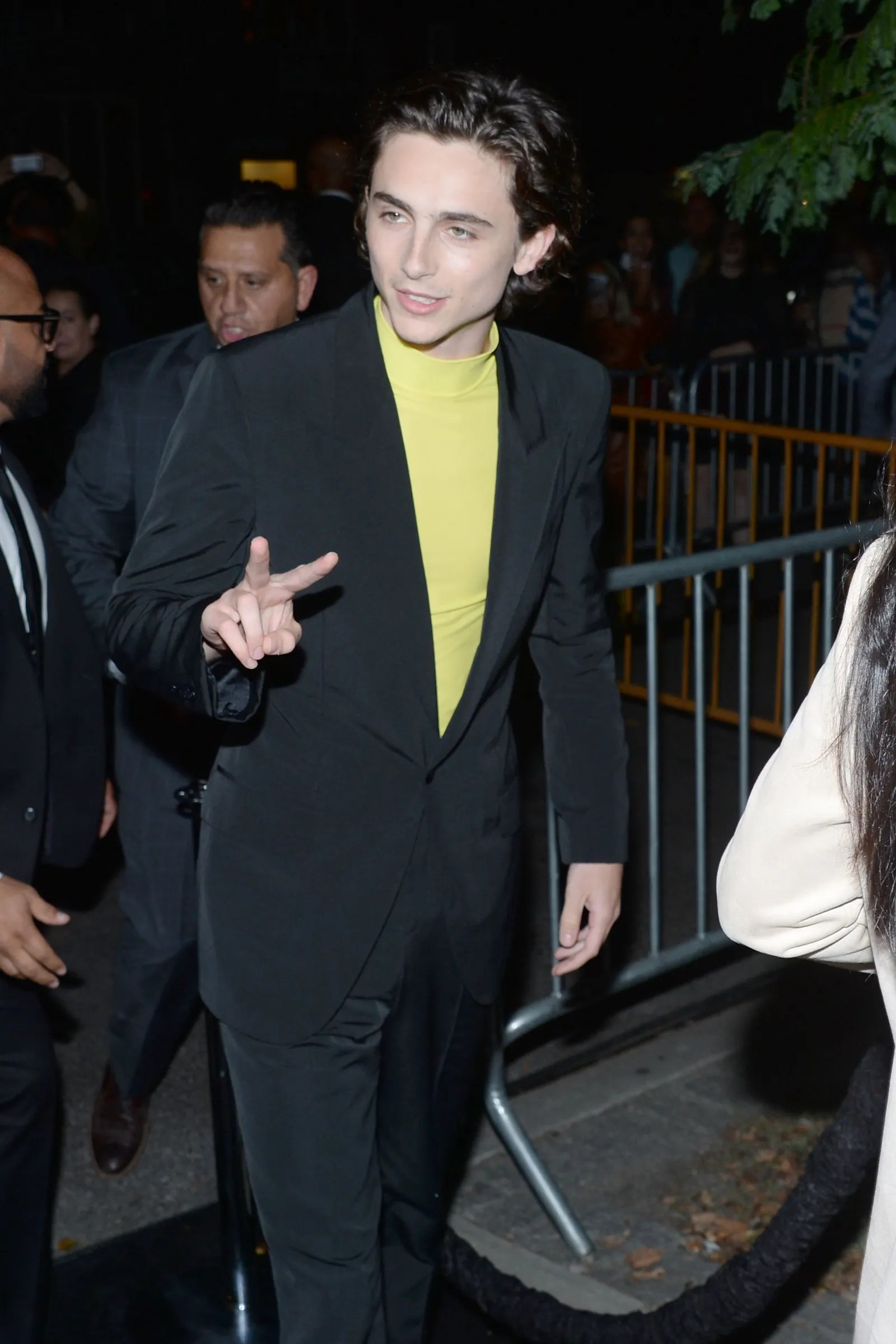 a man walking at night wearing a neon green turtleneck underneath a black blazer and pants holding up a peace symbol