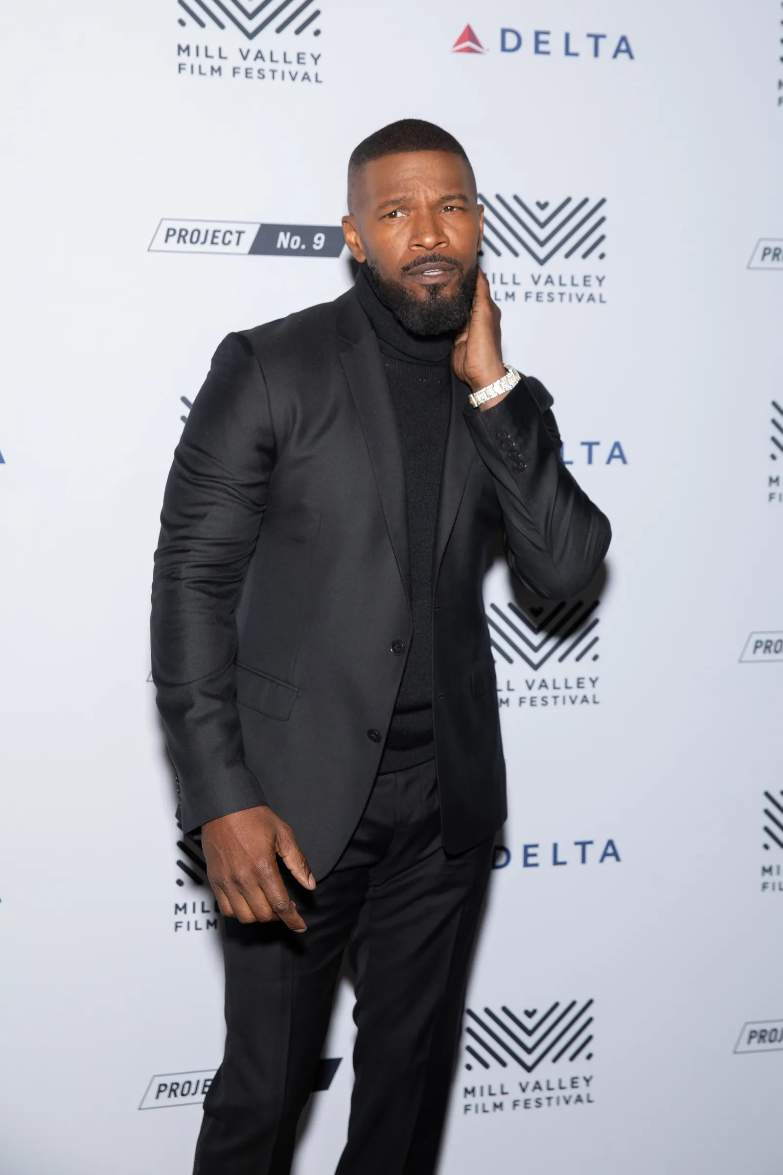 Jamie Foxx with a beard wearing all black raising one eyebrow and touching his cheek