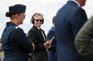 a man smiling wearing headphones and sunglasses