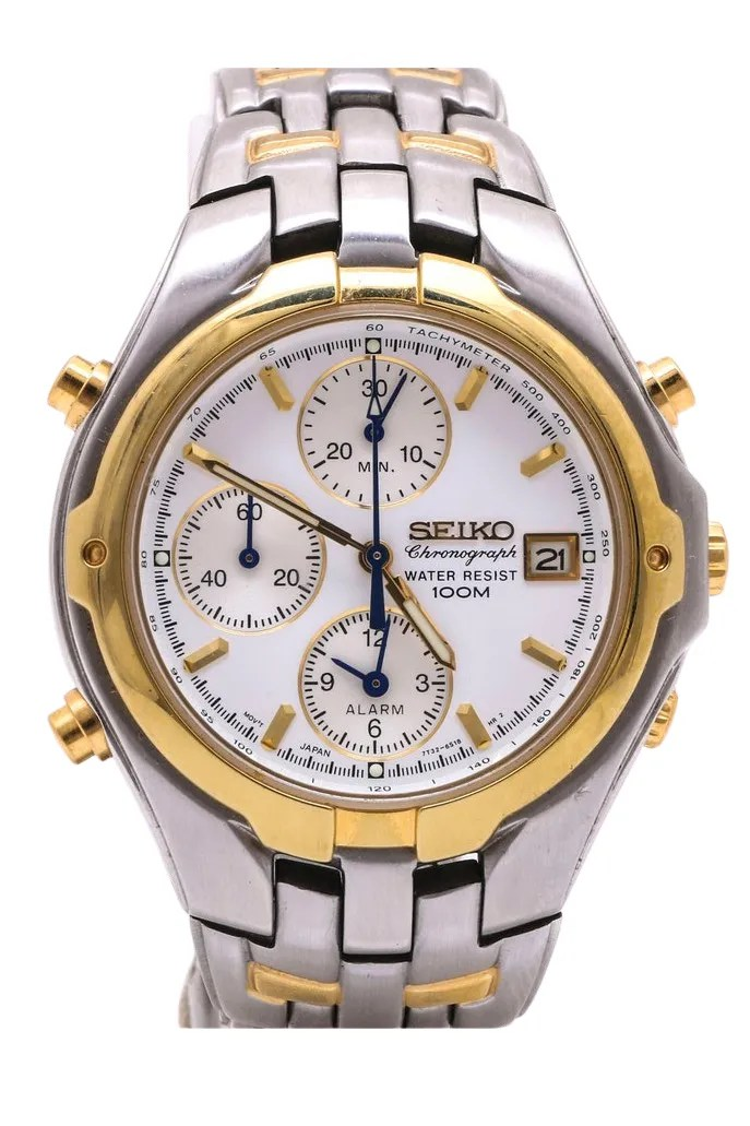 A steel watch with gold accents and a white face