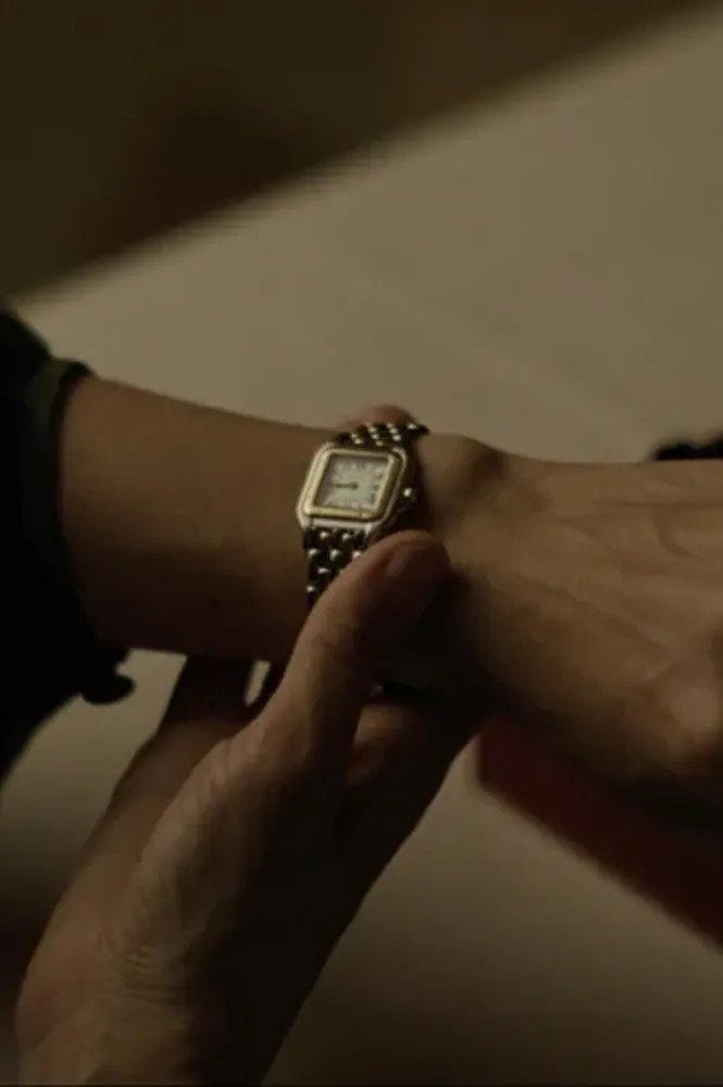 A person looking at their wrist wearing a gold square watch