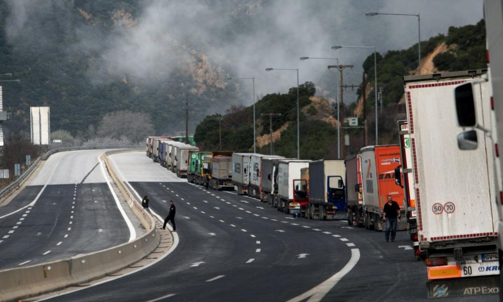 Lorry drivers stand next to a column of lorries blocked on a highway near the Promachonas border crossing between Greece and Bulgaria.