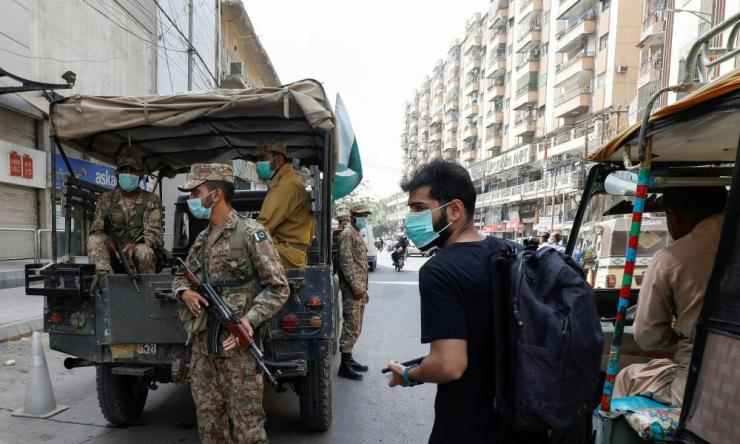 A resident wearing a protective mask walks past Pakistan Army soldiers on patrol to enforce coronavirus disease safety protocols in Karachi.