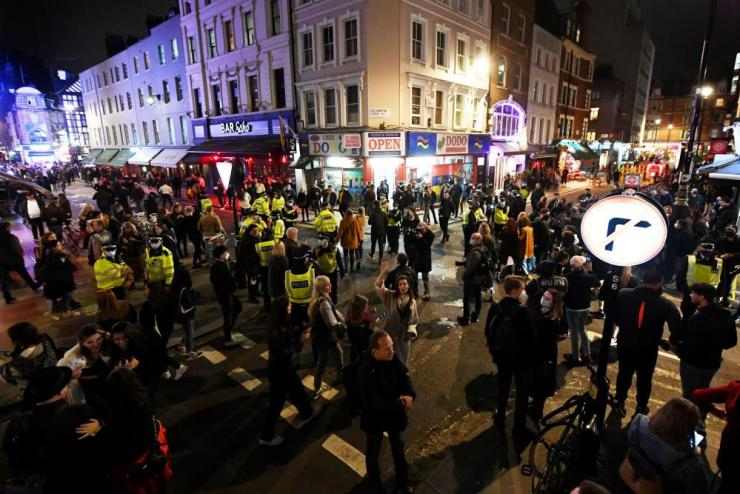 Police disperse people on Old Compton street in Soho at the 10pm curfew on 16 October, the night new tier 2 lockdown restrictions came into force in London.