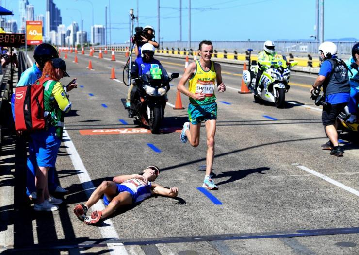 Michael Shelley of Australia (R) passes Callum Hawkins of Scotland (L) as he collapses after being in the lead of the Men's Marathon Final on day eleven of competition at the XXI Commonwealth Games.